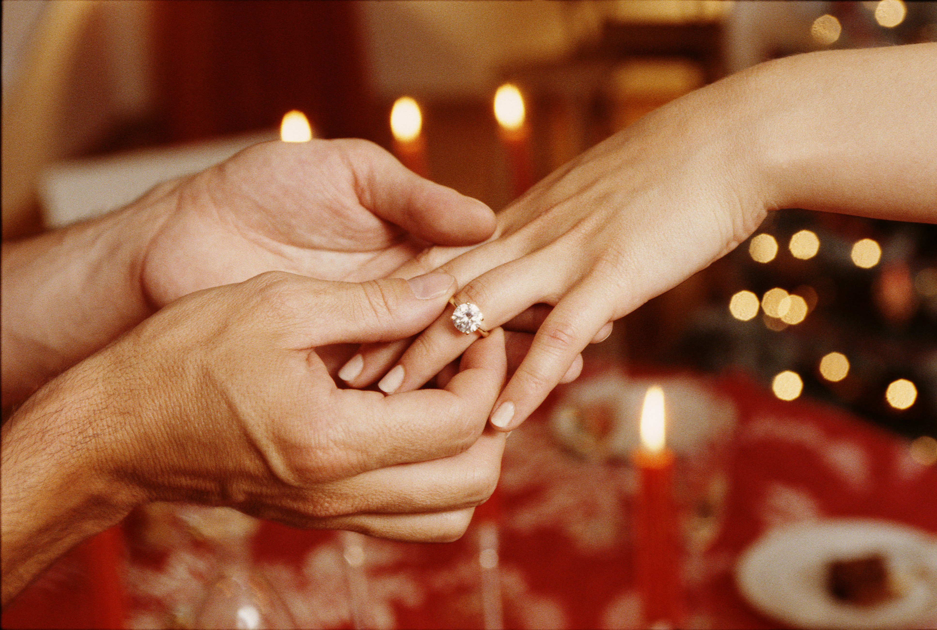 Man placing ring on woman's finger, close-up