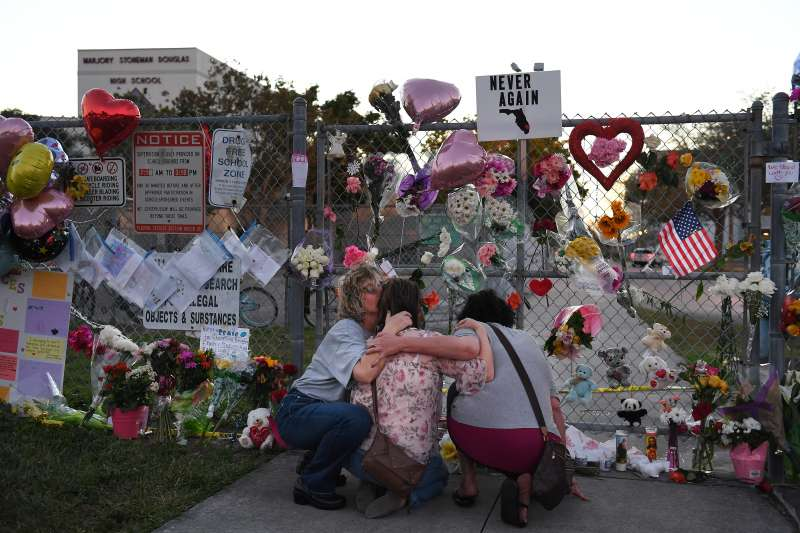 Three women embrace outside Marjory Stoneman Douglas High School on Sunday February 18, 2018 in Parkland, Florida.