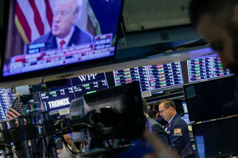 Traders work on the floor of the New York Stock Exchange (NYSE) as U.S. President Donald Trump is seen on TV on March 1, 2018 in New York City. Major stock indexes plunged Thursday afternoon following President Trump's announcement that he was imposing a 25 percent tariff on imported steel and 10 percent on aluminum. Investor concern about the news rattled the Dow Jones industrial average, which closed down more than 400 points.