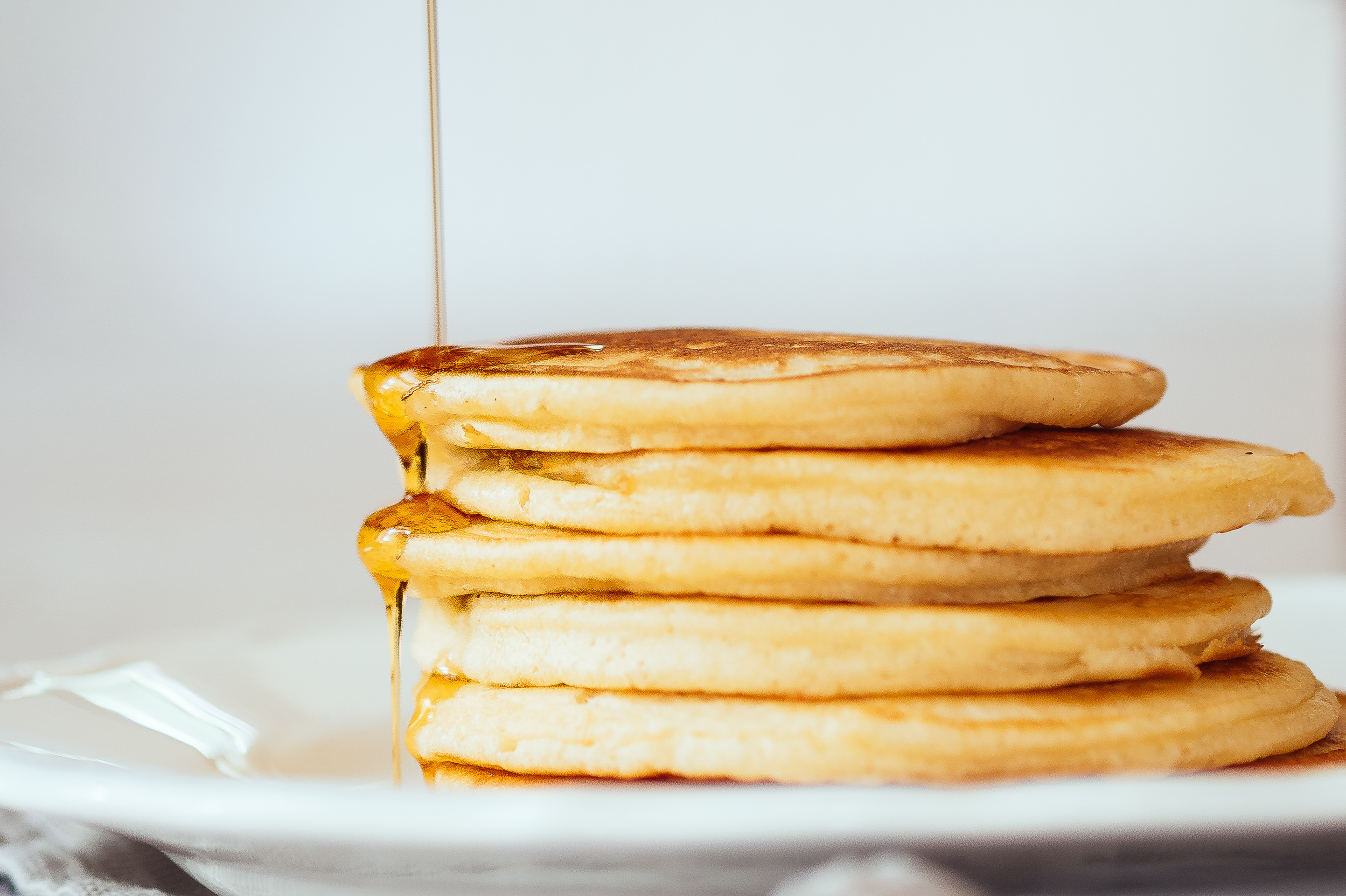Maple Syrup Falling On Pancakes Served In Plate On Table