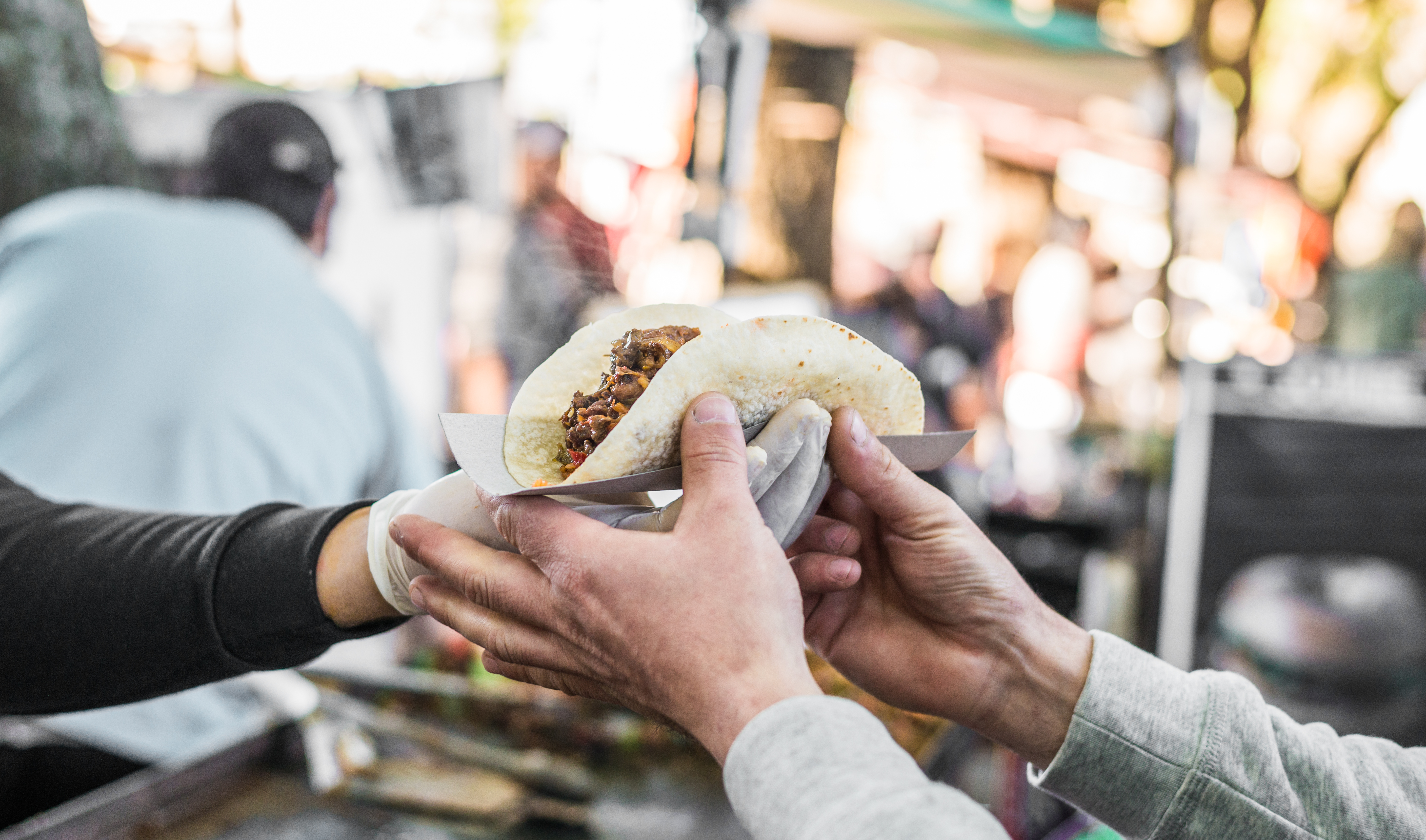 Chef handing a taco to a foodie at a street food market