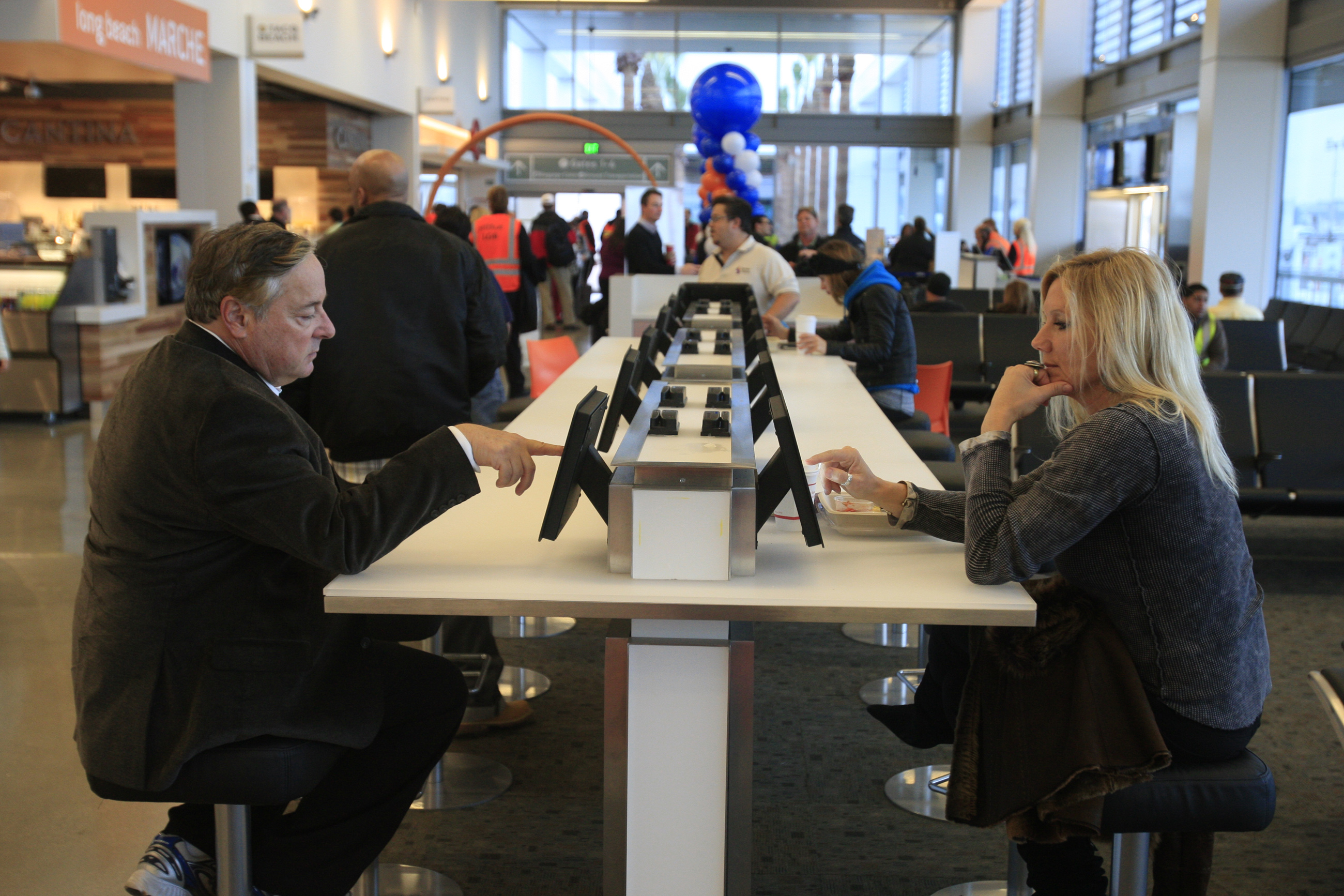 Travelers Steve Gould, left, of Tustin, and Diane Armitage, of Laguna Beach, check out new iPads wh