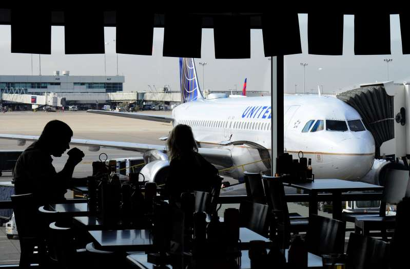 Airline passengers eat in a terminal cafe as a United Airlines passenger plane is parked at a gate at Denver International Airport in Denver, Colorado.