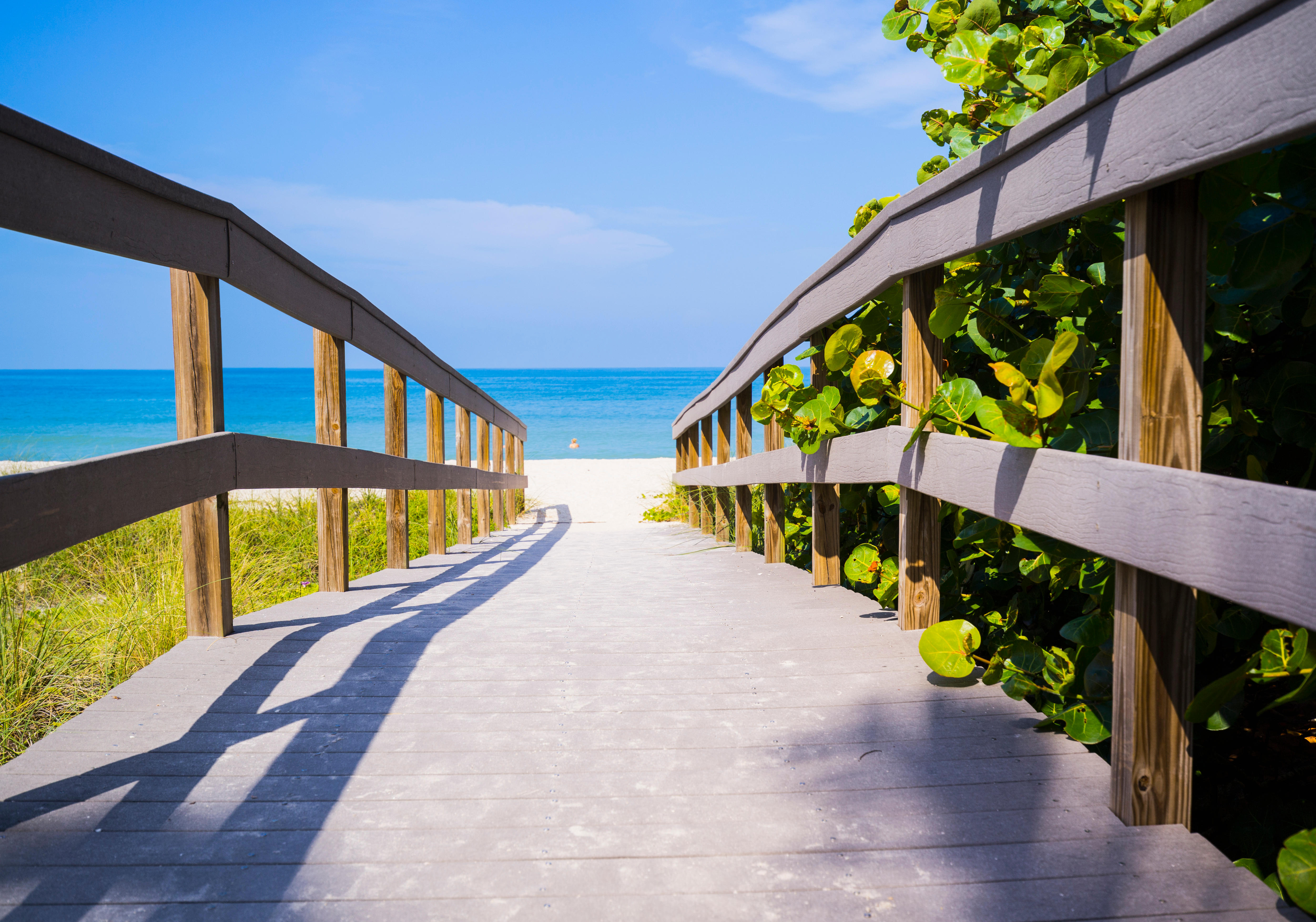 Florida, USA - Wooden boardwalk to ocean on Sunset Beach, Treasure Island, Florida on Gulf of Mexico in summer