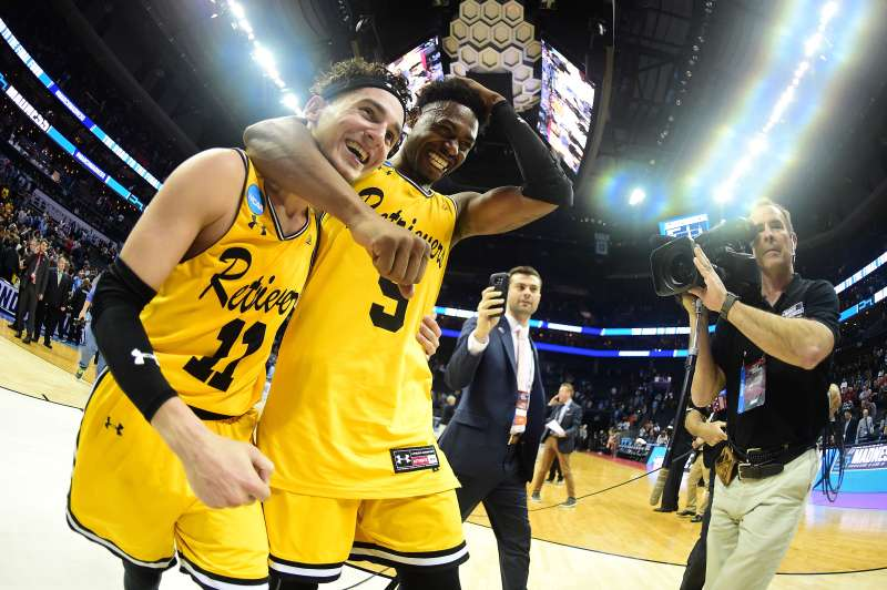 K.J. Maura #11 and teammate Jourdan Grant #5 of the UMBC Retrievers celebrate their 74-54 victory over the Virginia Cavaliers during the first round of the 2018 NCAA Men's Basketball Tournament at Spectrum Center on March 16, 2018 in Charlotte, North Carolina.