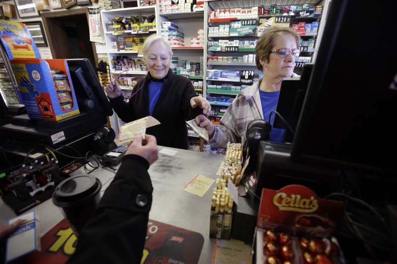 Cashiers Kathy Robinson, left, and Ethel Kroska, right, both of Merrimack, N.H., sell a lottery ticket, to Diane Ackley, hand only below, at Reeds Ferry Market convenience store, in Merrimack.