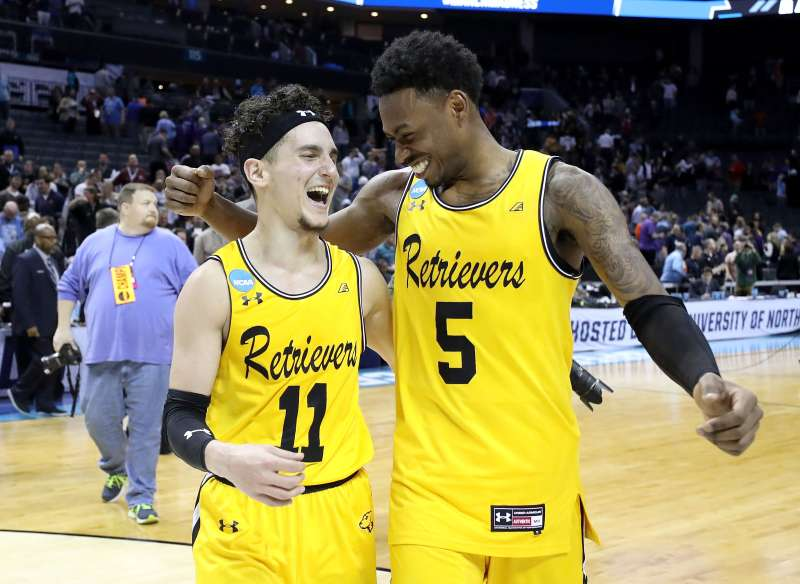 K.J. Maura (#11) and Jourdan Grant (#5) of the UMBC Retrievers celebrate their 74-54 victory over the Virginia Cavaliers during the first round of the 2018 NCAA Men's Basketball Tournament at Spectrum Center on March 16, 2018 in Charlotte
