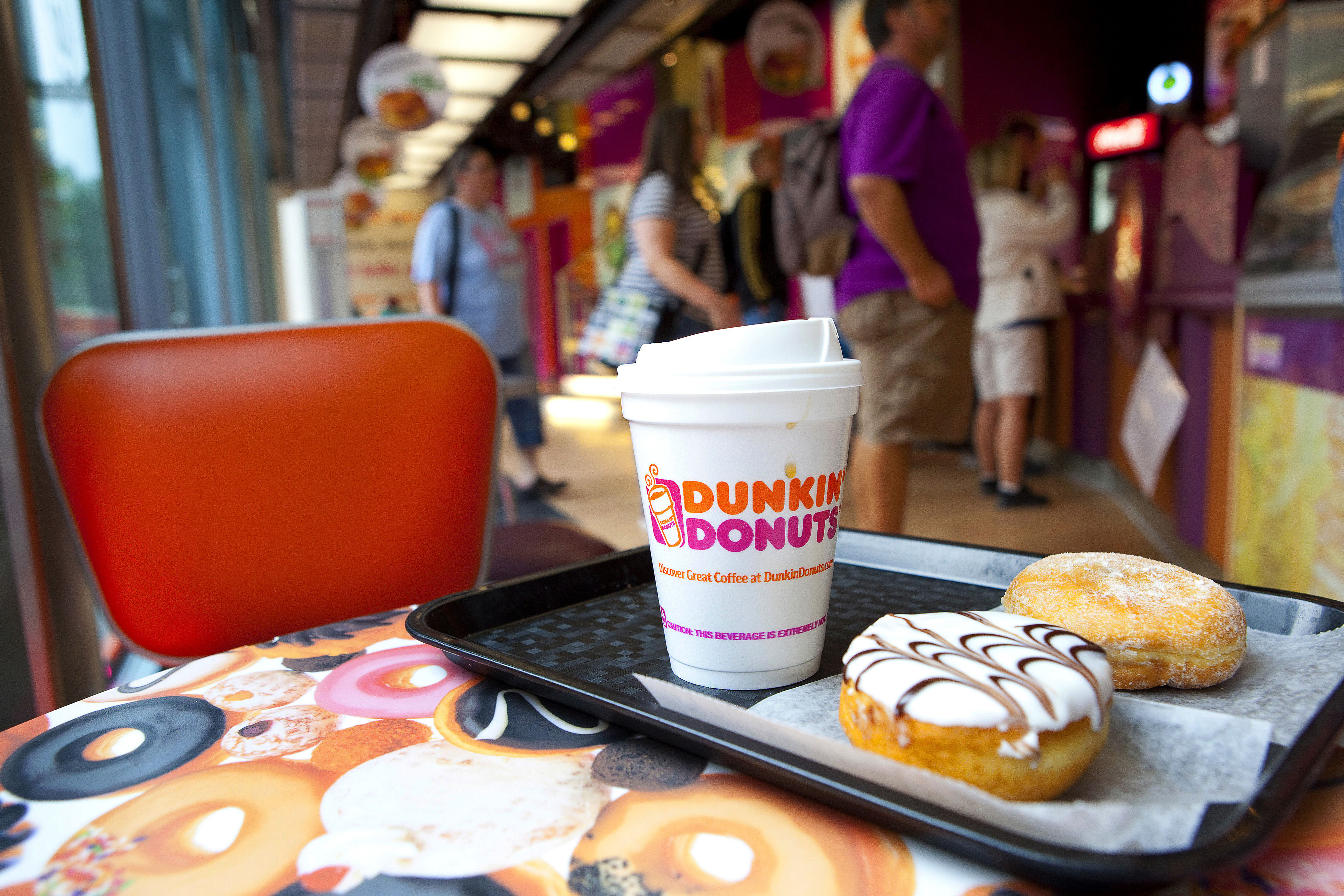 Doughnuts and a beverage cup are seen on a tray as customers wait to be served at a sales counter in this arranged photograph taken inside a Dunkin' Donuts store, operated by Dunkin' Brands Group Inc., in Berlin, Germany, on Aug. 19, 2013.