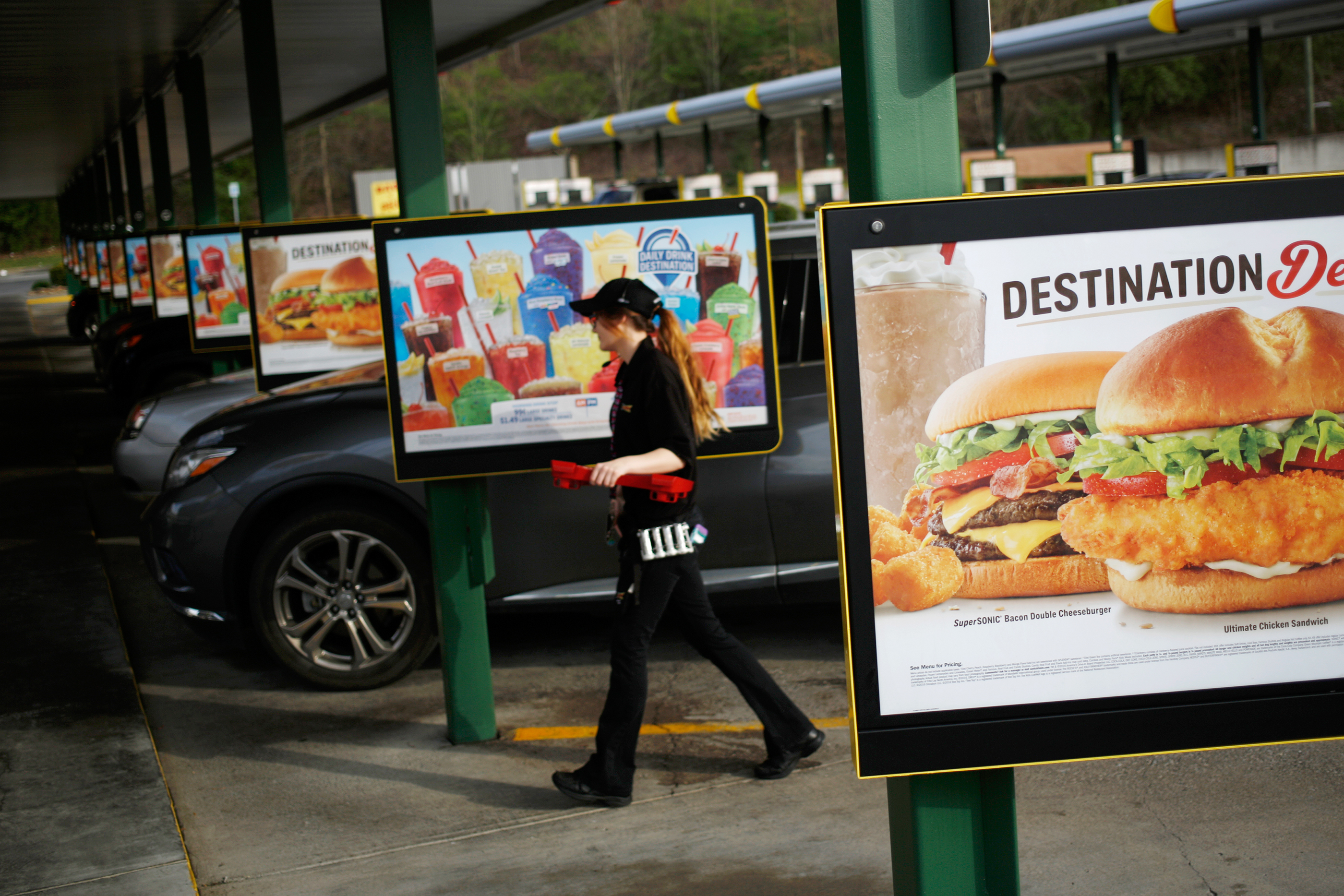 A carhop walks through the parking lot after delivering food to a customer at a Sonic Corp. drive-in fast food restaurant in Knoxville, Tennessee, on March 25, 2017.