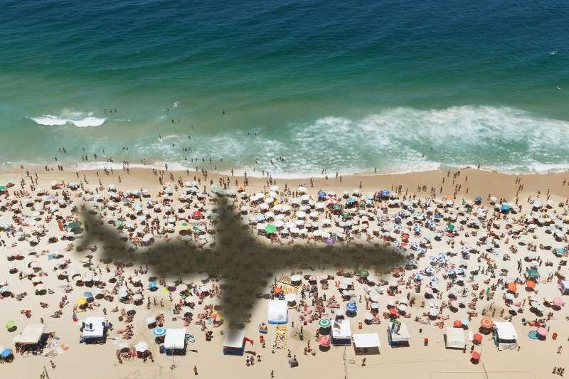 A plane flies over a beach near Rio de Janeiro, Brazil, November 15, 2013.