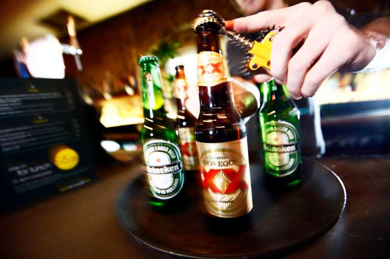 A barman opens a bottles of Dos Equis and Heineken beer at a public house in London, U.K., on Monday, Jan. 11, 2010.