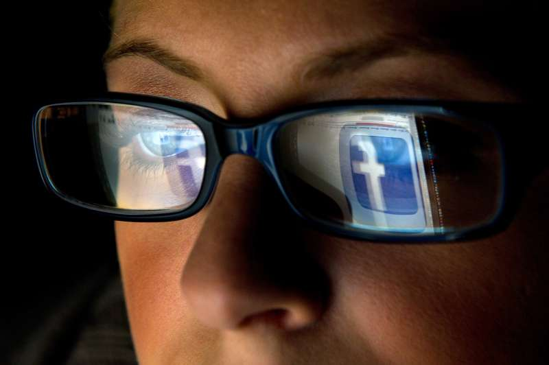The Facebook Inc. logo is reflected in the eyeglasses of a user in San Francisco, California, U.S., on Wednesday, Dec. 7, 2011.