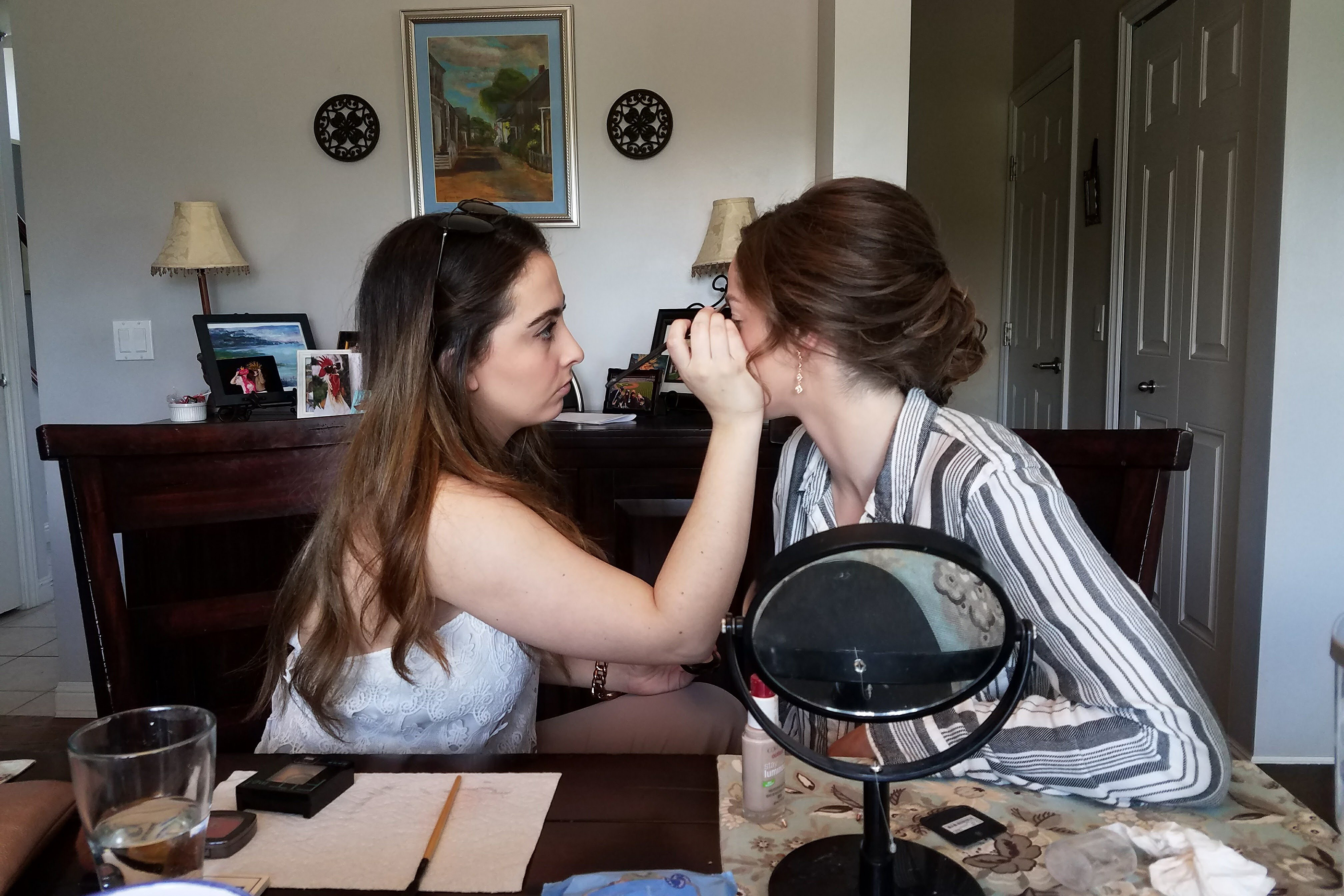 Katherine Crapps gets her makeup done by her friend, Giovanna Scappaticci, for her prom in 2017.