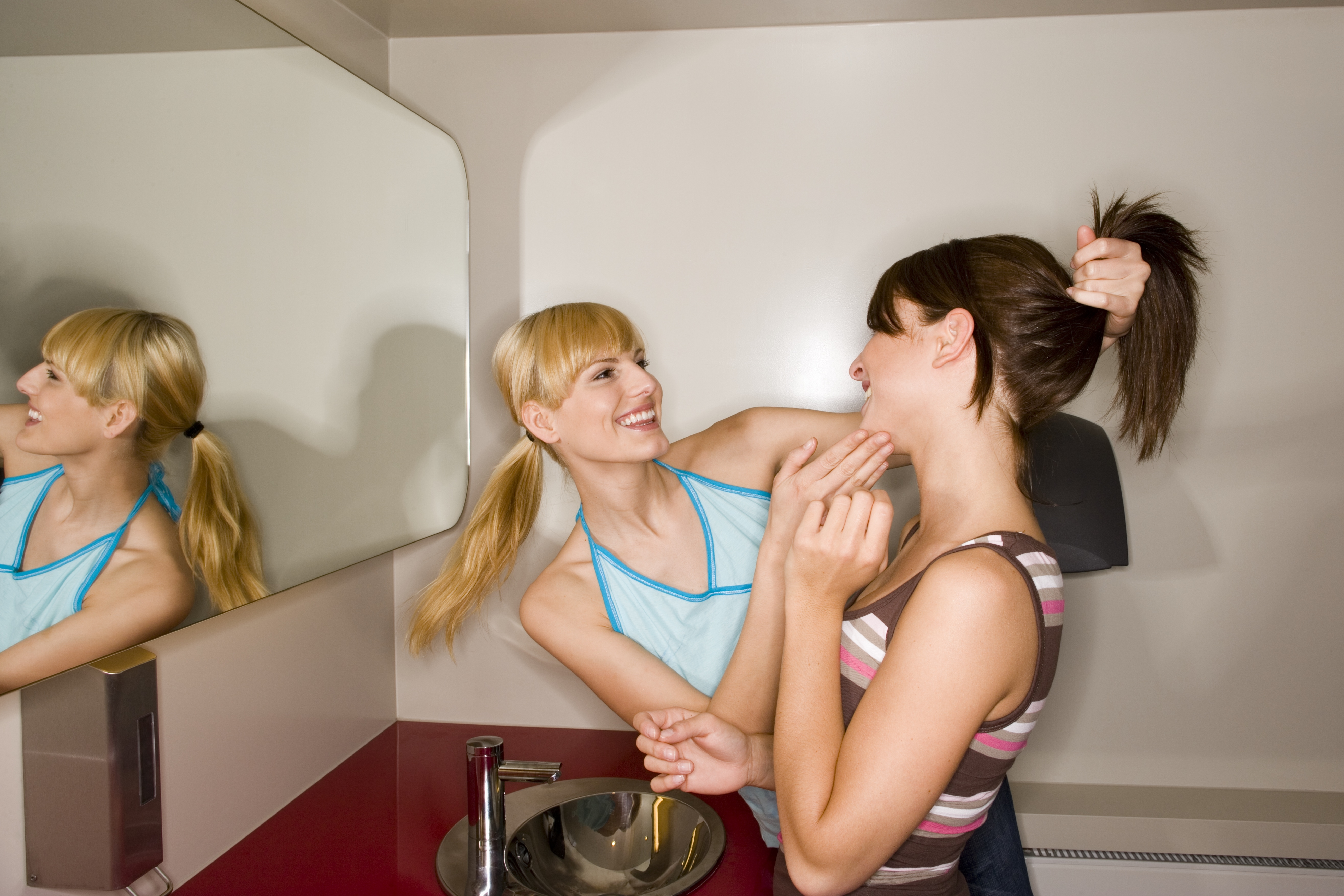 Woman fixing friend's hair in public restroom
