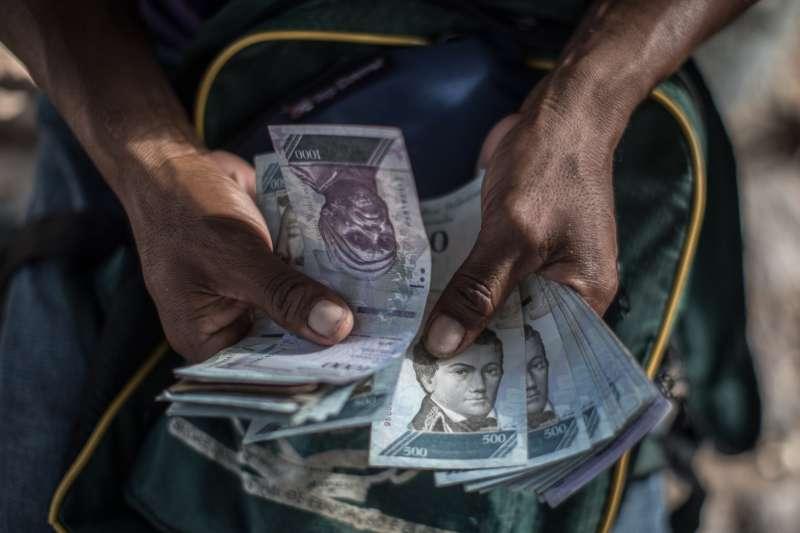 A Venezuelan migrant holds out Bolivar banknotes
