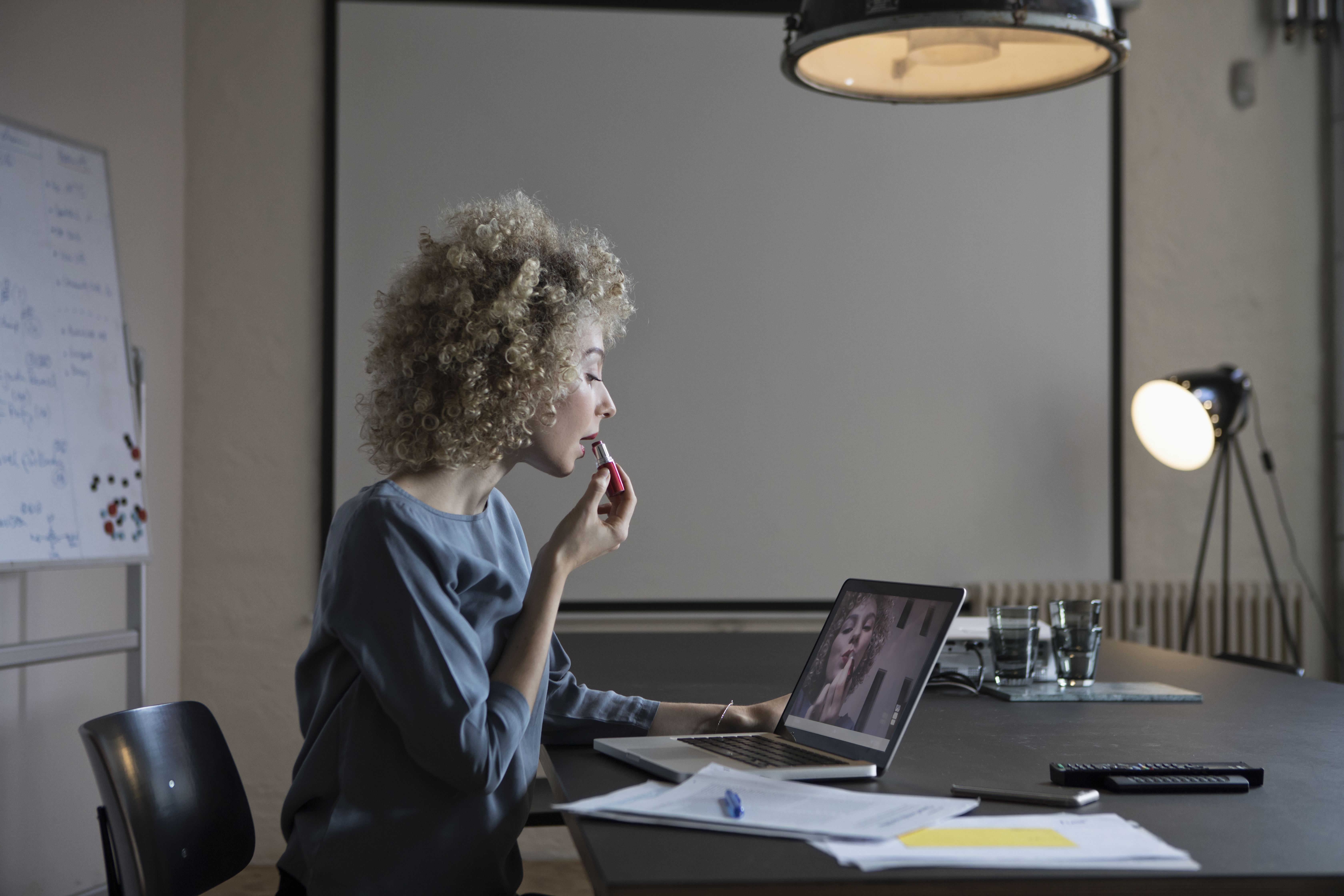 Woman in office applying make-up using laptop monitor as mirror