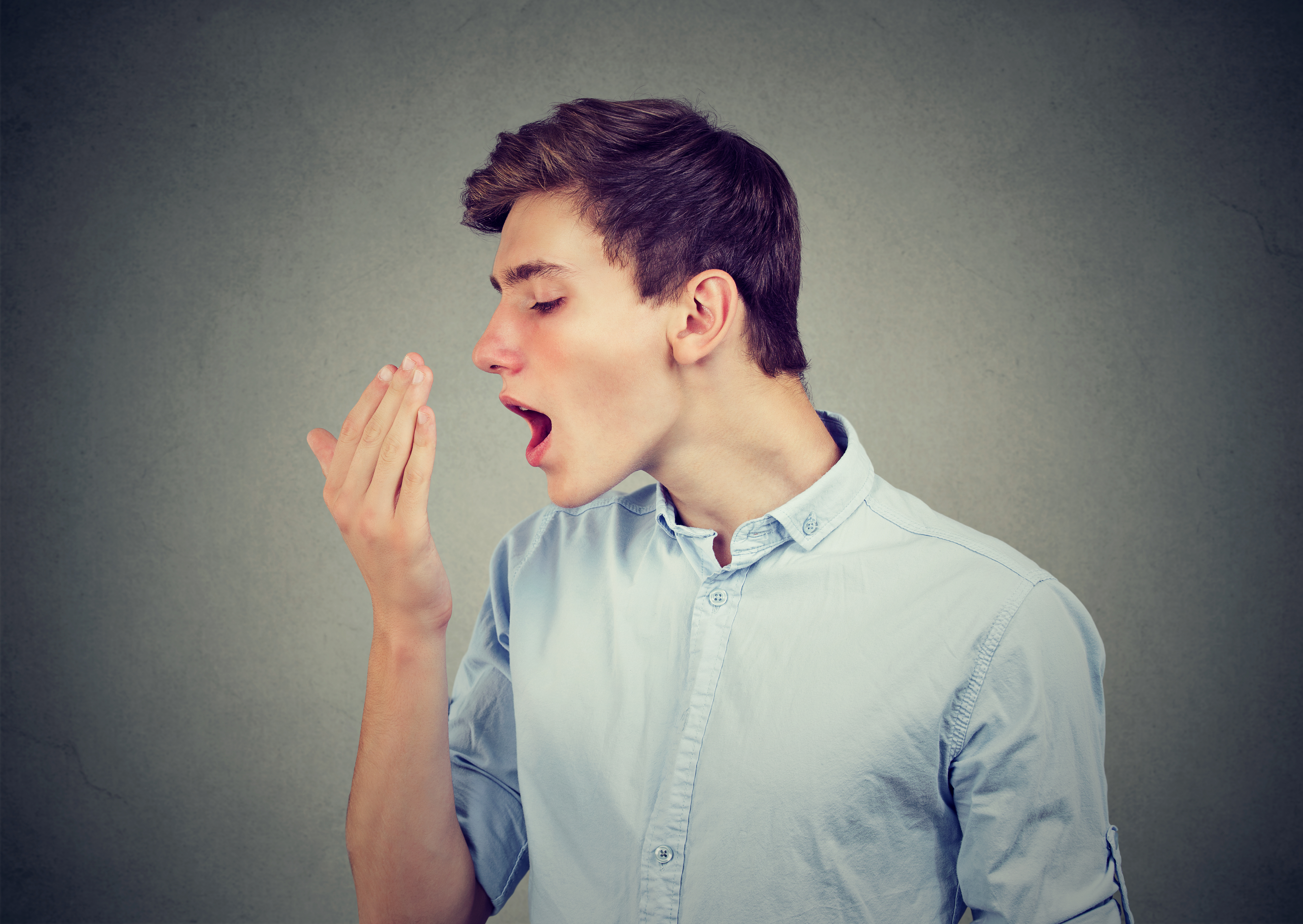 Young man checking his breath with hand.