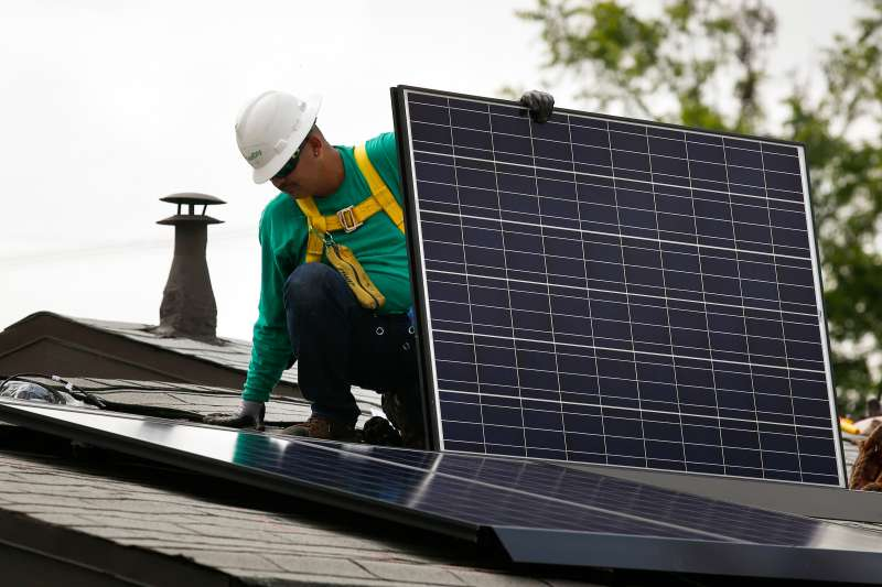 An employee installs a solar panel on the roof of a home in Los Angeles. Photographer: Patrick T. Fallon/Bloomberg via Getty Images