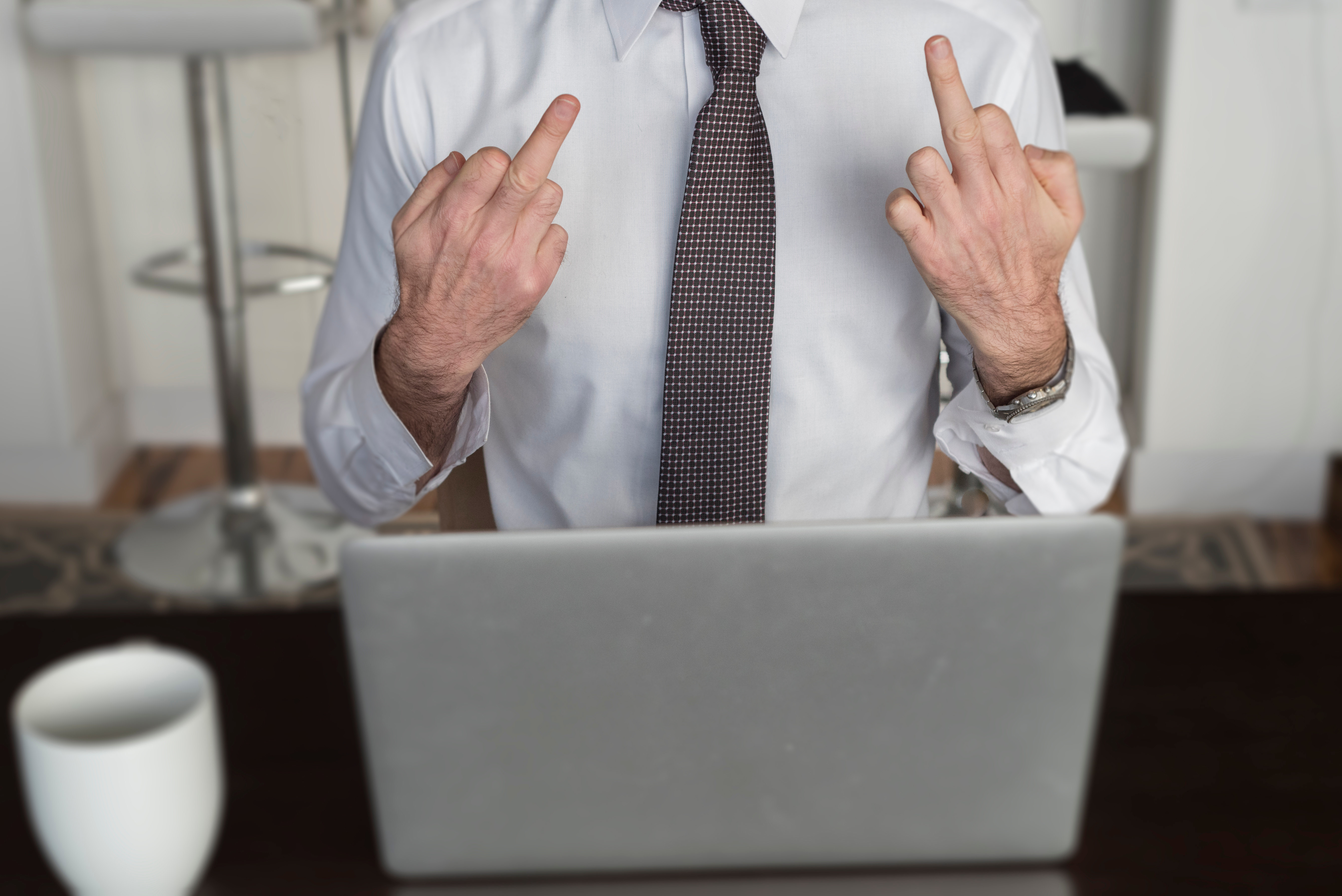 Close-Up Of Man Working Showing Middle Finger To Laptop Screen