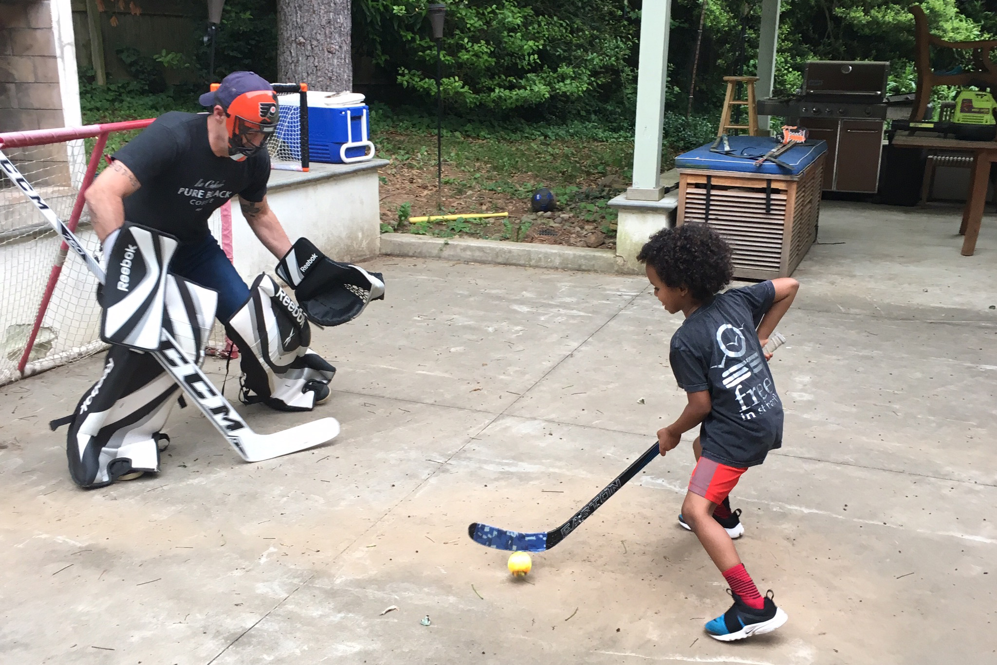 Todd Carmichael playing street hockey with his son, Ben