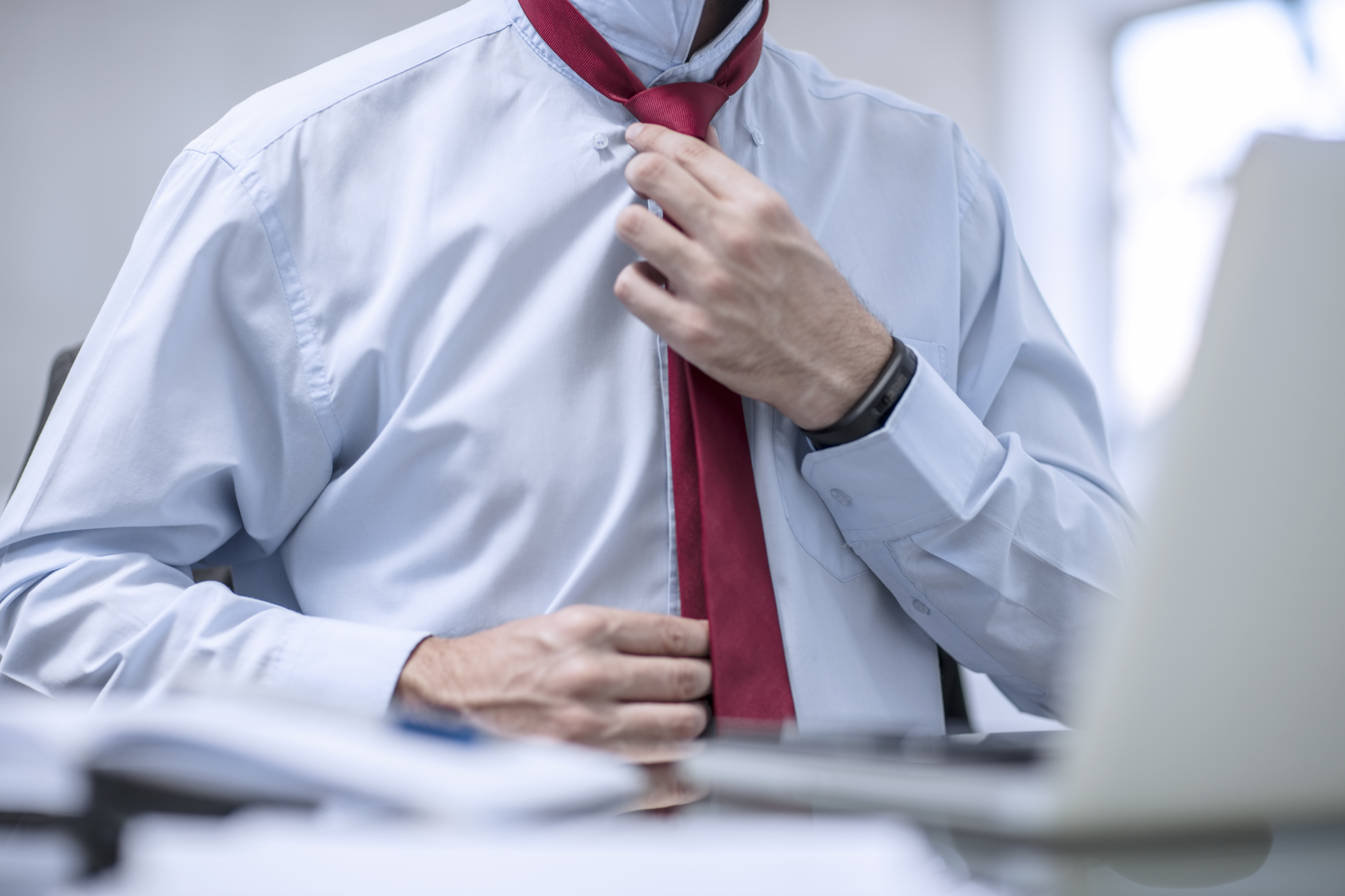 Person in office fixing his red tie