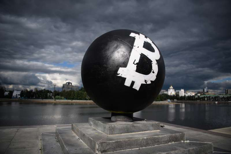 YEKATERINBURG, RUSSIA - JULY 25, 2017: The Bitcoin cryptocurrency symbol on a stone sphere monument painted black