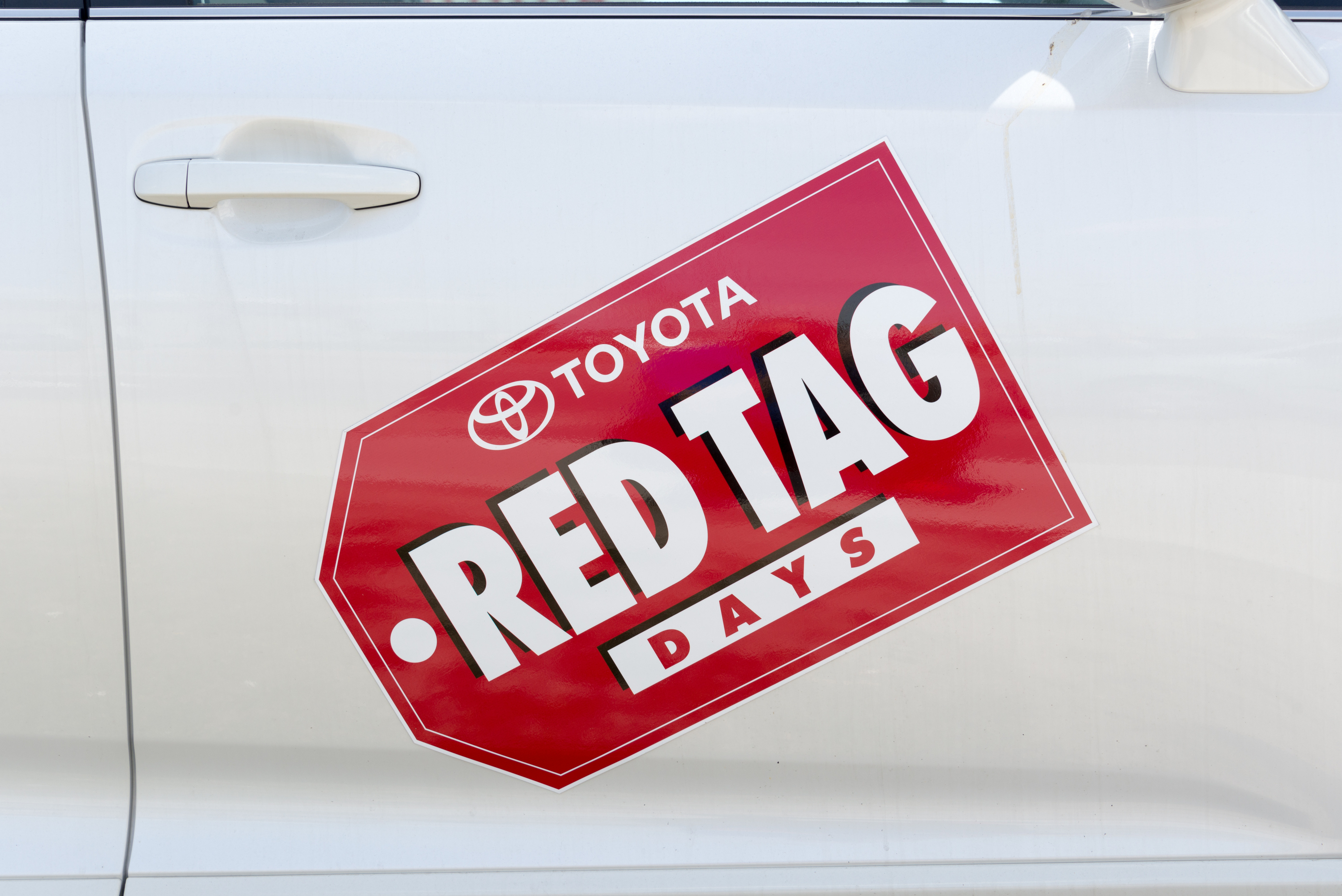 Toyota Red Tag Days sale sticker shown on passenger door of