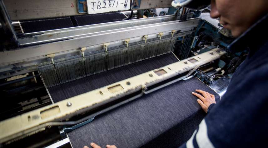 A man works a weaving machine at the Momotaro Jeans  in Kurashiki, Japan.