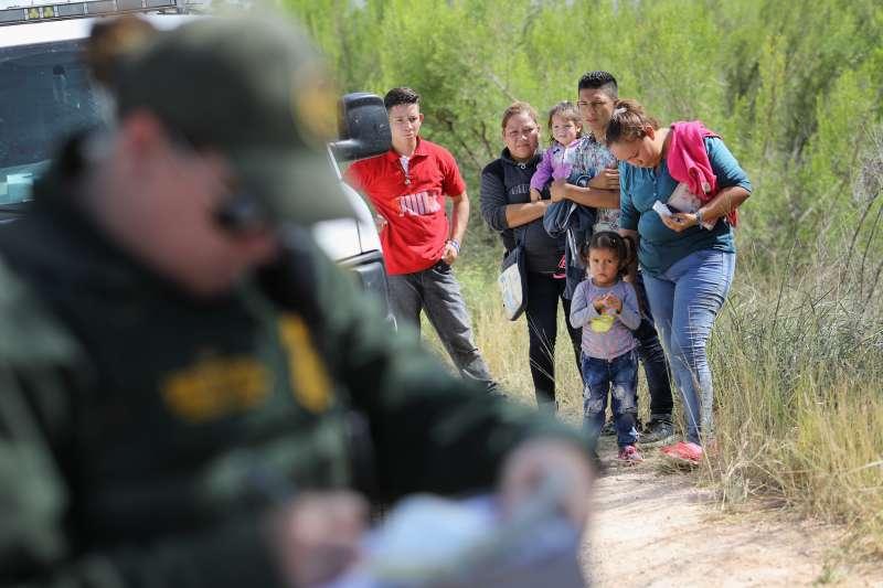 Central American asylum seekers wait as U.S. Border Patrol agents take groups of them into custody on June 12, 2018 near McAllen, Texas.