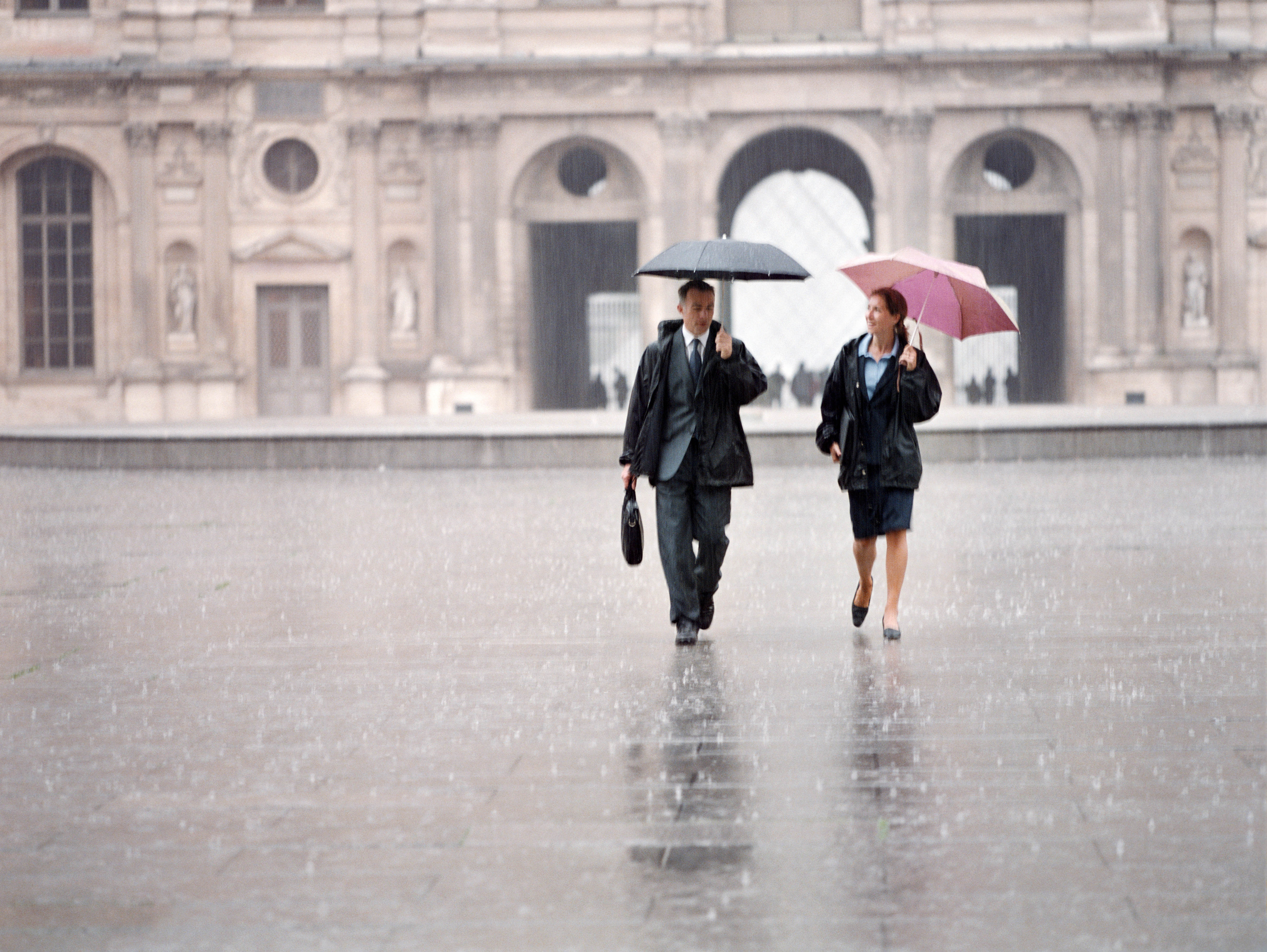Business colleagues walking together in the rain