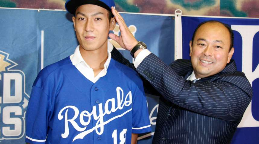 In this July 8, 2018, photo, Kaito Yuki, left, poses with Hiroyuki Oya, a Royals international scout, for photographers at a press conference in Osaka, western Japan. Yuki is headed to the Kansas City Royals organization instead of attending high school in Japan. The team signed Yuki, a 16-year-old pitcher, out of junior high to a standard seven-year minor league contract Sunday. He is thought to be the first Japanese junior high school player to sign with a major league club.
