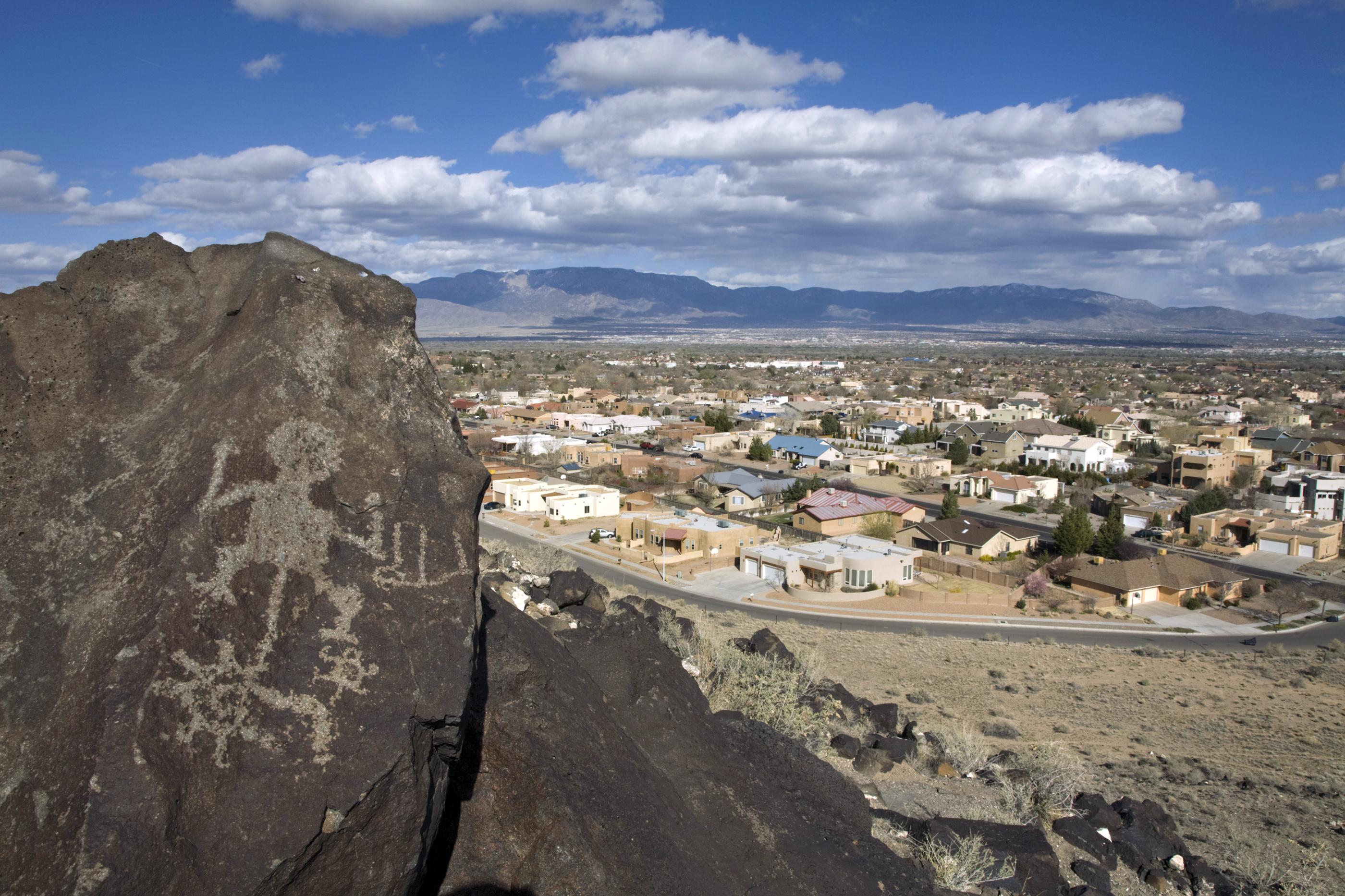 Prehistoric petroglyphs and heavy urbanization in the background.