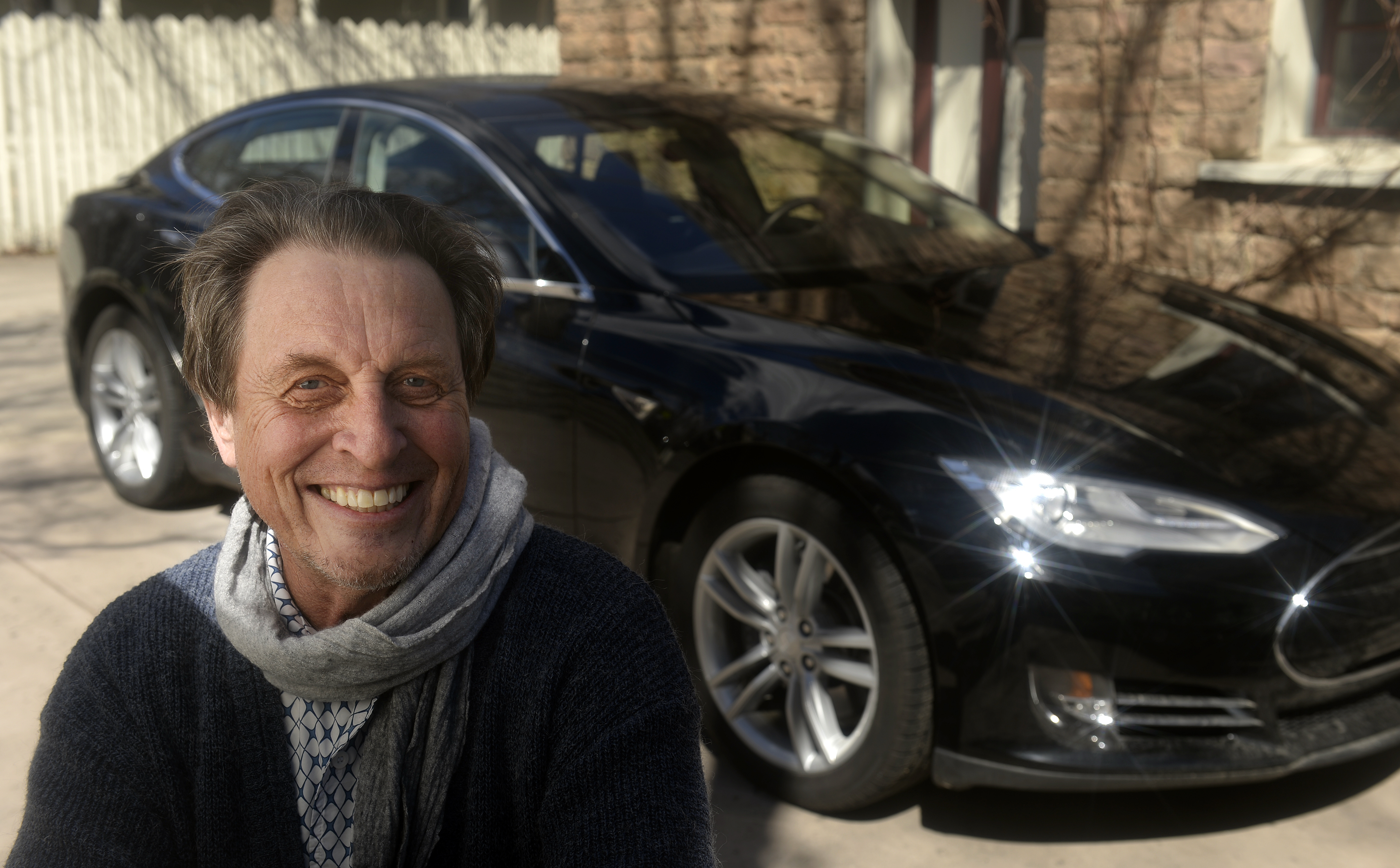 South African Errol Musk who the father of billionaire entrepreneur Elon Musk. In the background is a Tesla Model S.