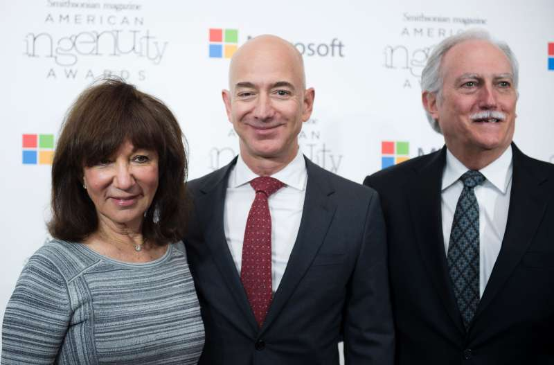 Amazon CEO Jeff Bezos poses on the red carpet with his parents Mike and Jackie, for the Smithsonian Magazine's 2016 American Ingenuity Awards on December 8, 2016 in Washington, DC.  Mike and Jackie Bezos might be worth millions due to their early investments in their son's company.