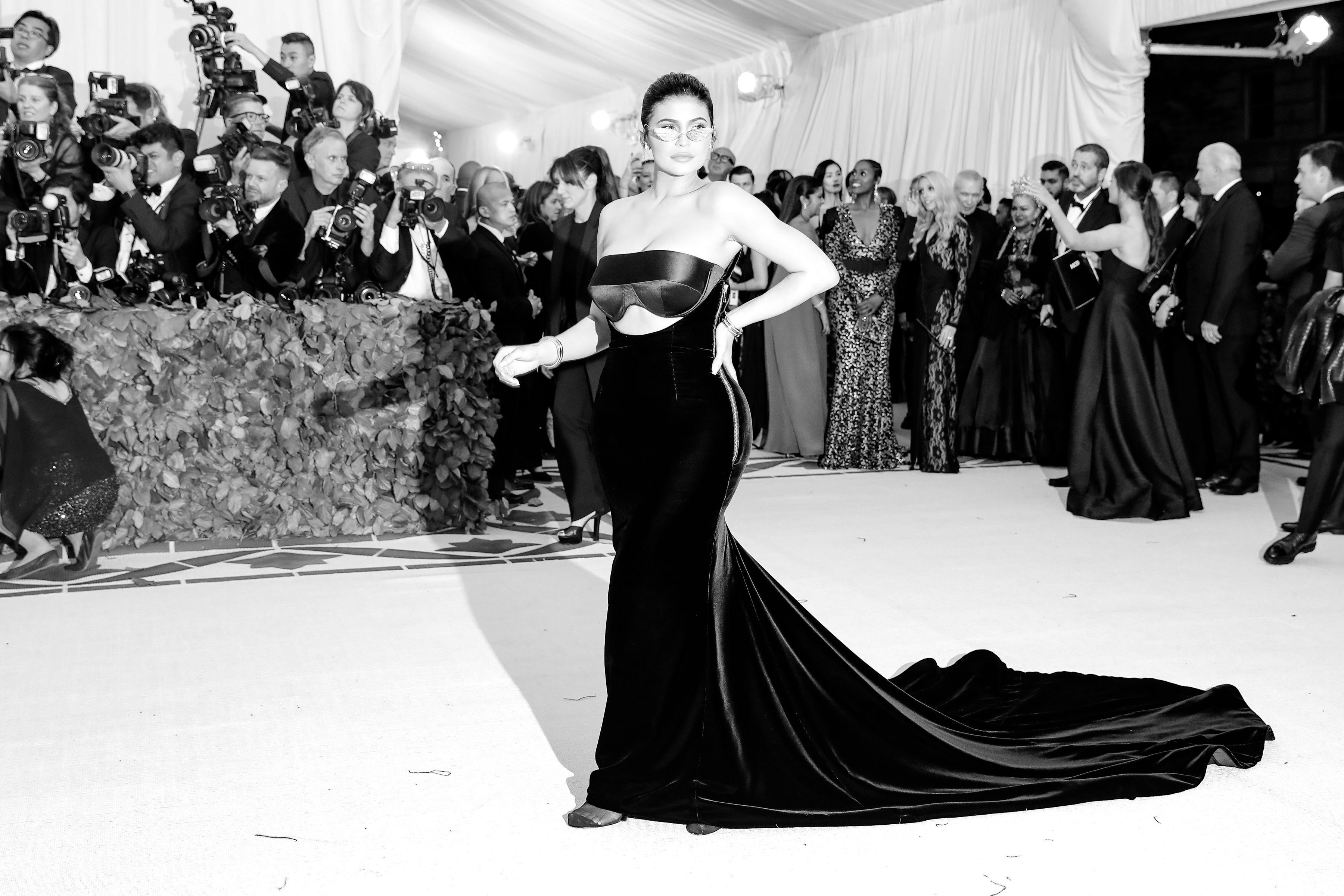 A black and white photo of Kylie Jenner on the red carpet, wearing a floor-length black gown with a long train.