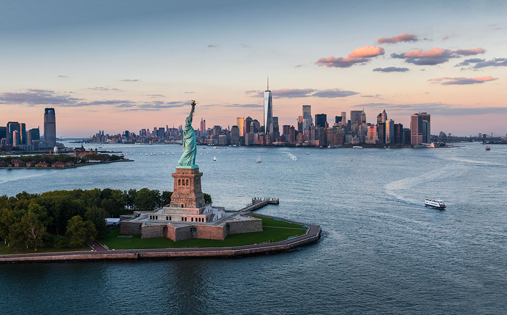 Aerial view of city with Statue of Liberty at sunset