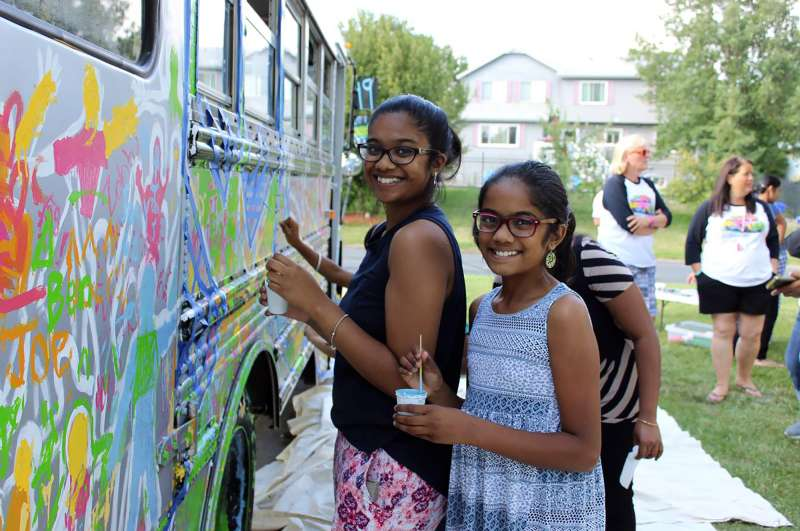"Residents come out to decorate a mobile classroom in Woodbury during the ""Paint the Bus"" event."