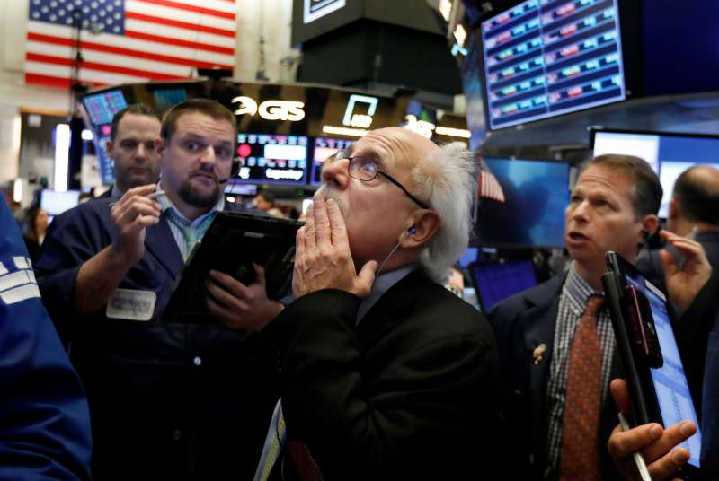 Peter Tuchman, center, works with fellow traders on the floor of the New York Stock Exchange, . Stocks are opening broadly lower on Wall Street, a day after a massive surge, as a number of big companies reported disappointing results               Financial Markets Wall Street, New York, October 26, 2018.