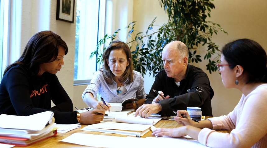 Gov. Jerry Brown reviews a measure with his wife, Anne Gust Brown, second from left, as staff members Camille Wagner, left, and Graciela Castillo-Krings, right, look on at his Capitol office, Sunday, Sept. 30, 2018, in Sacramento, Calif. Sunday is the last day for Brown to approve or veto bills passed by the legislature. Brown, who will be leaving office in January, is acting on some on the last pieces of legislation in his tenure as governor.