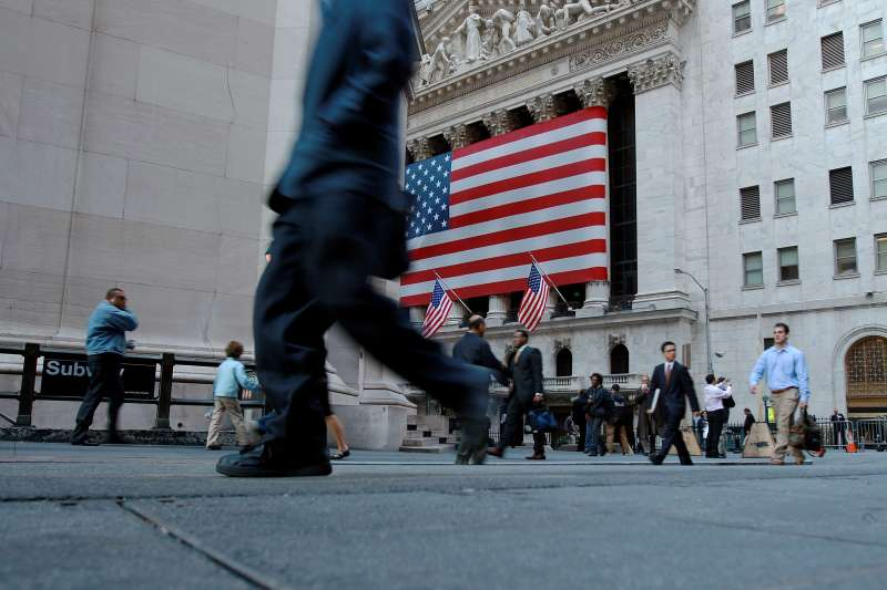 Pedestrians walk down Wall St. across from the New York Stock Exchange