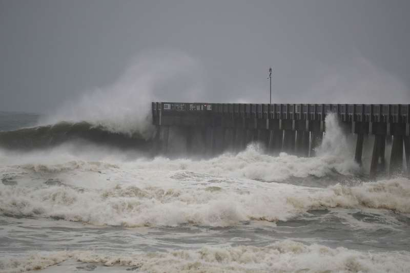 Waves crash along a pier as the outerbands of Hurricane Michael arrive on October 10, 2018 in Panama City Beach, Florida.