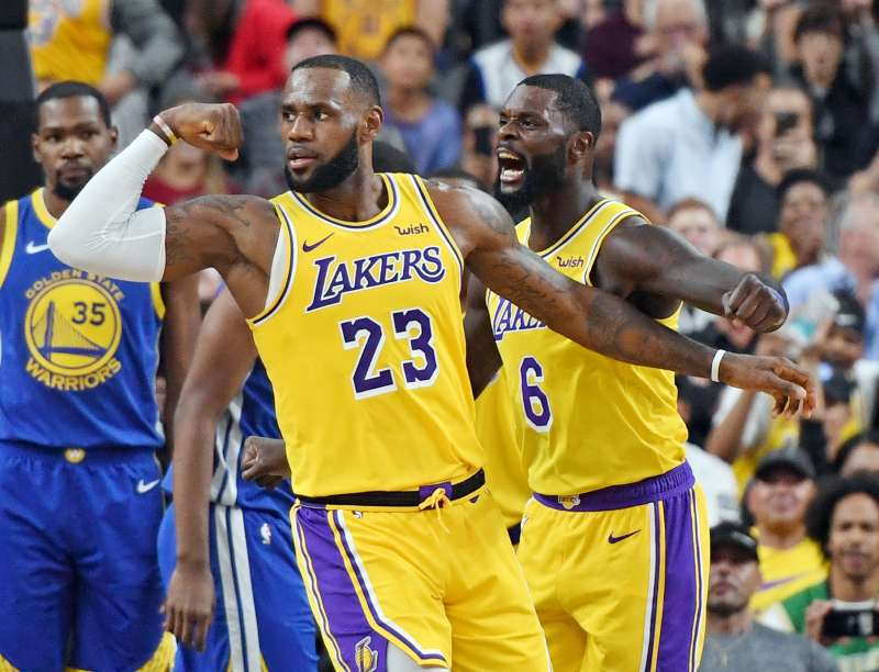 LeBron James #23 and Lance Stephenson #6 of the Los Angeles Lakers celebrate after James made a shot against the Golden State Warriors during a preseason game.