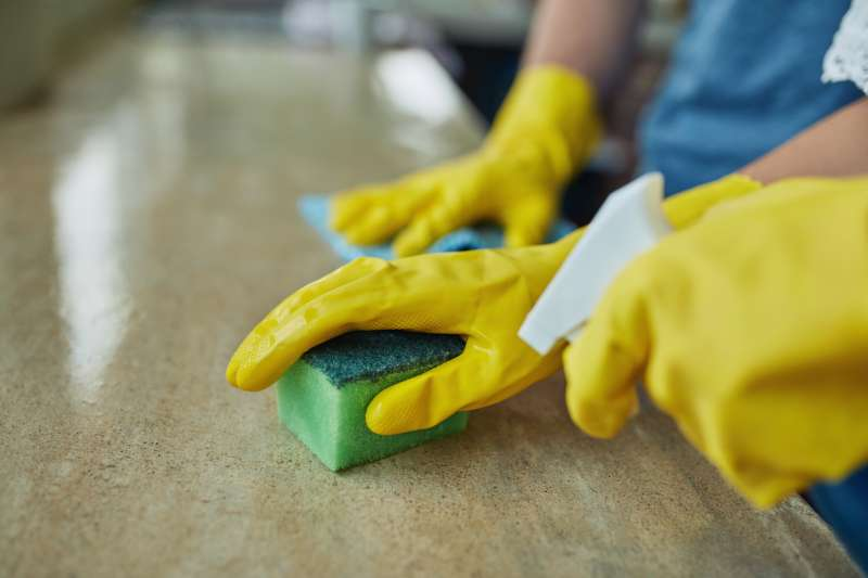 Closeup shot of an unrecognizable couple cleaning a surface at home