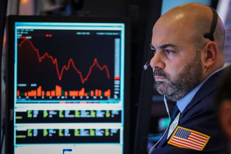 A trader works at his desk at the closing bell on the floor of the New York Stock Exchange (NYSE)