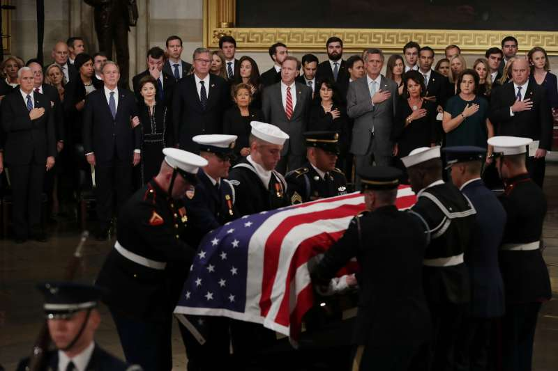 The family of former U.S. President George H.W. Bush stand as his flag-draped casket is carried into the U.S. Capitol Rotunda on December 03, 2018 in Washington, D.C.
