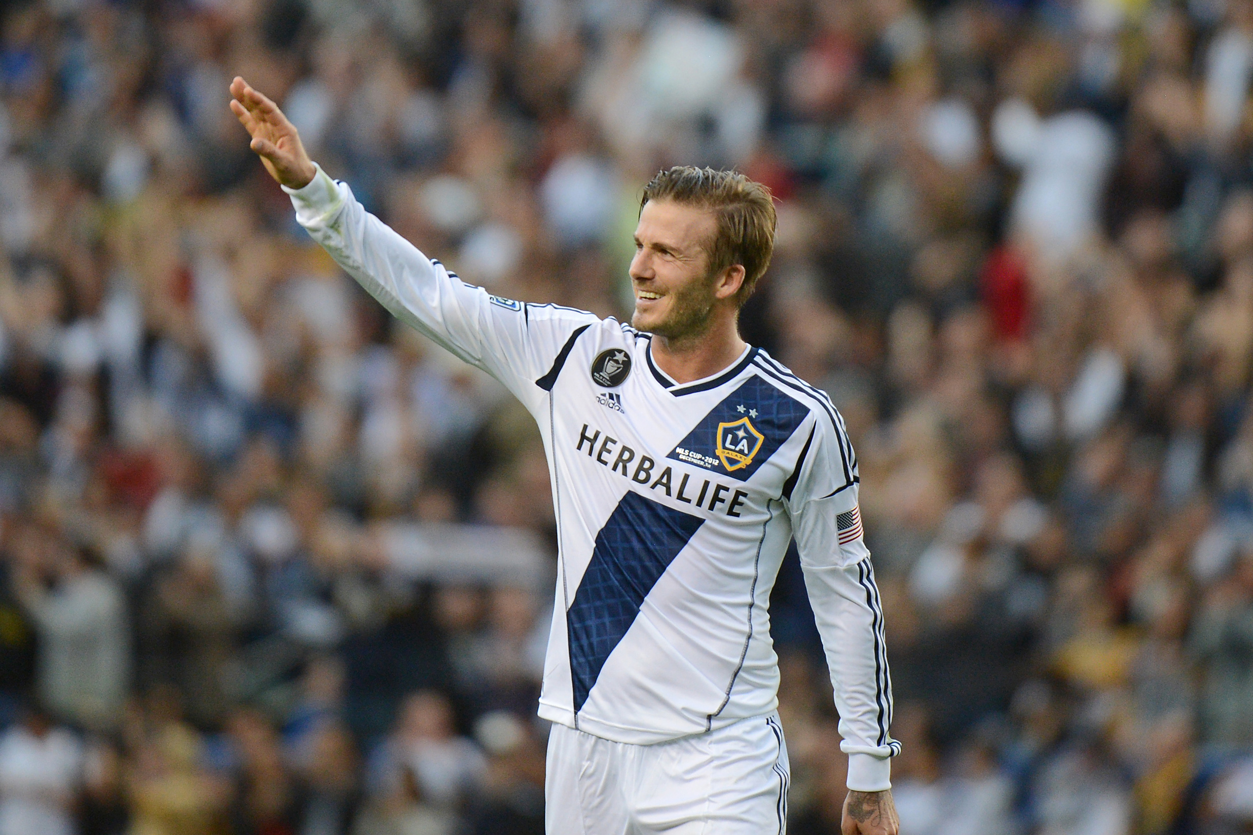 David Beckham waves to fans as he walks off the pitch after the Los Angeles Galaxy defeat the Huston Dynamo in the Major League Soccer (MLS) Cup, December 1, 2012 in Carson, California. It was Beckham's last game with the Galaxy.