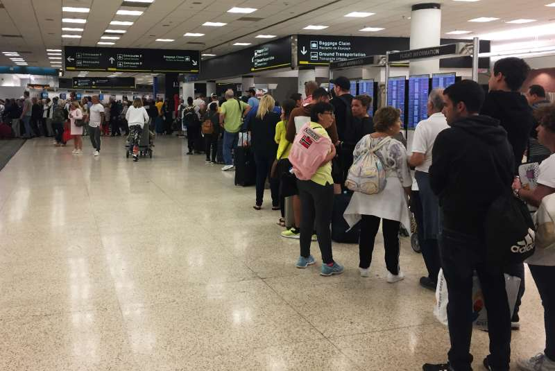 Passengers flying from Miami International Airport wait in line to enter the checkpoint at Concourse F, where some of the flights of a closed terminal were diverted, on January 13, 2019.
