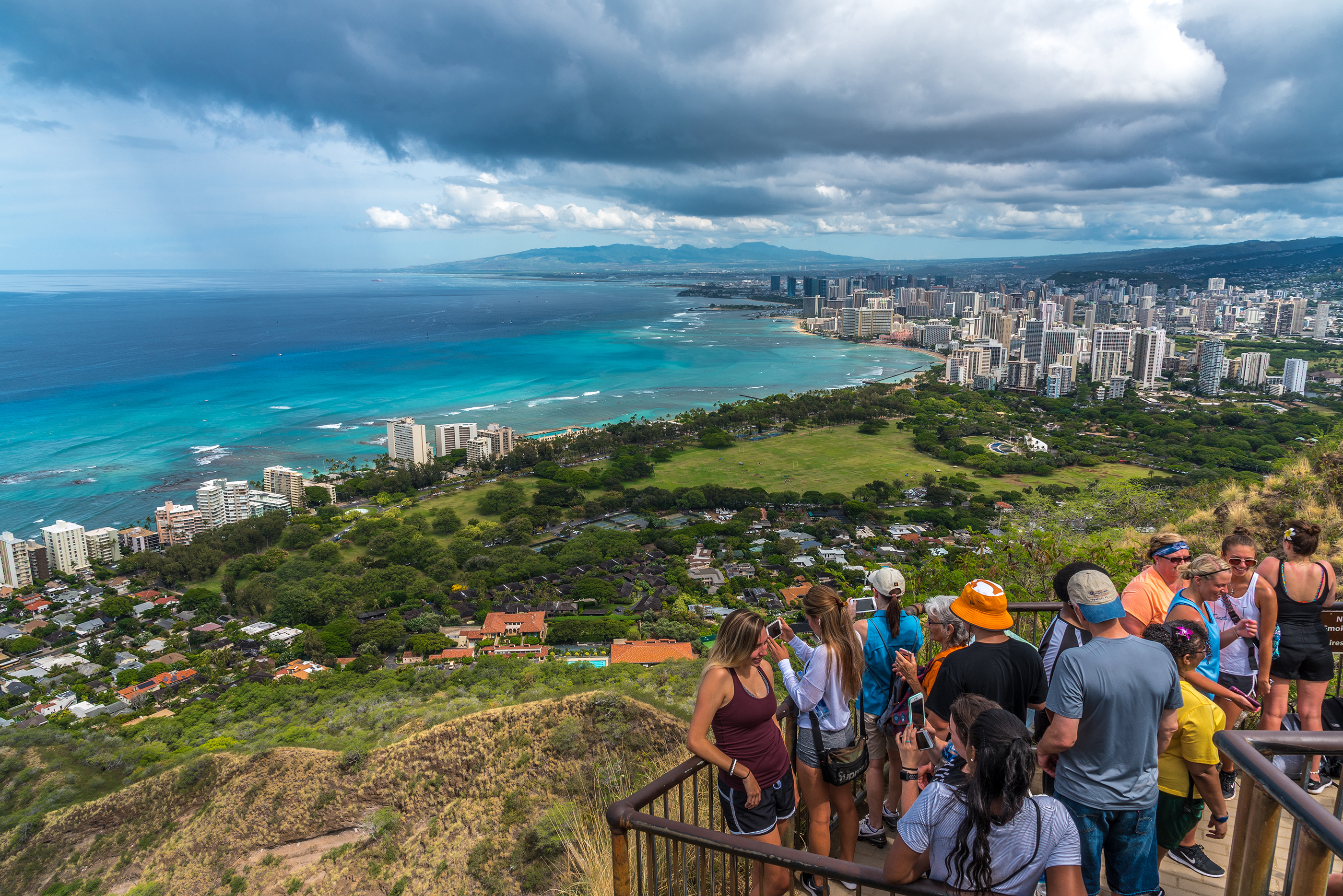 Agroup of tourists take selfies and photos of Waikiki and greater Honolulu from the top of the Diamond Head crater landmark.