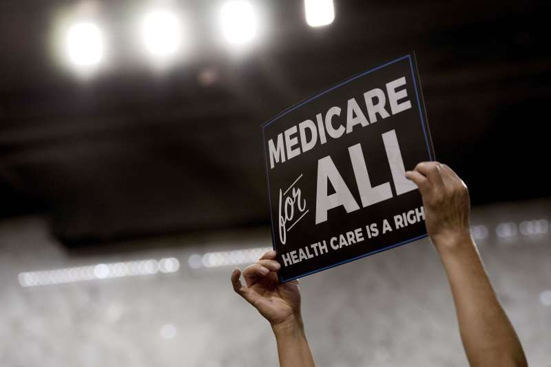 A member of the audience holds up a placard as US Senator Bernie Sanders, Independent from Vermont, discusses Medicare for All legislation on Capitol Hill in Washington, DC, on September 13, 2017.                            The former US presidential hopeful introduced a plan for government-sponsored universal health care, a notion long shunned in America that has newly gained traction among rising-star Democrats. / AFP PHOTO / JIM WATSON        (Photo credit should read JIM WATSON/AFP/Getty Images)