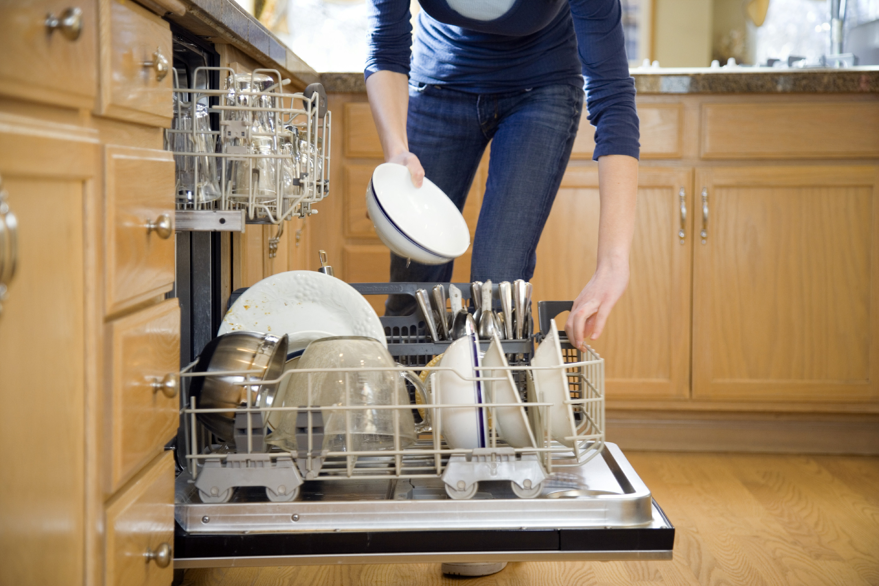 Teenage girl (16-18) putting dishes in dishwasher, low section